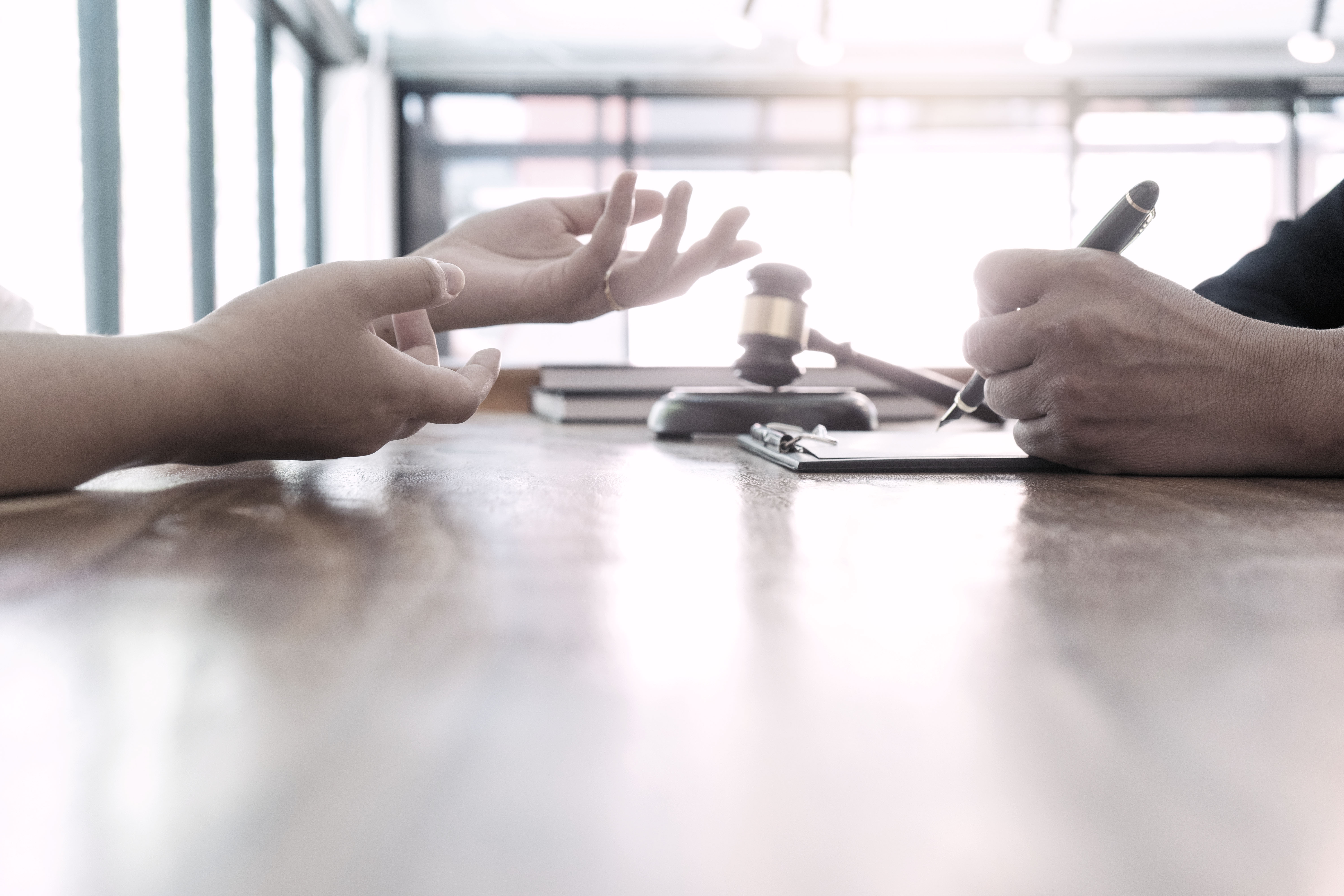 Two business people's hands are shown while they have a discussion at a desk
